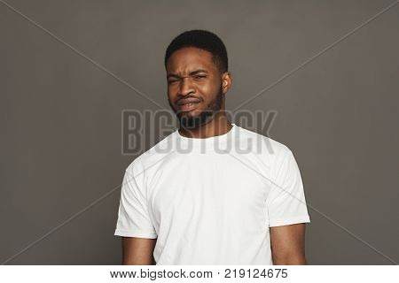 Black man expressing fear and disgust on face, grimacing on grey studio background. Negative emotions