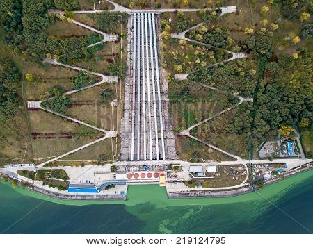 Gateway of Kyiv Pumped-Storage Power Plant. On the its sides there are green trees, power lines. Top view panoramic photo. Horizontal.