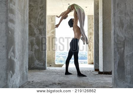 Topless dancer holds a ballerina over his head on the concrete floor of the unfinished building on the cityscape background. Man wears a black dance pants, girl wears a green leotard. Horizontal.