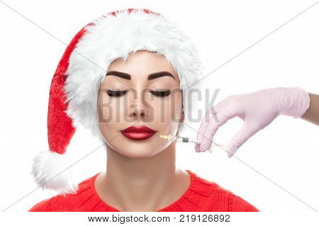 The doctor cosmetologist makes the botulinum injection procedure for tightening and smoothing wrinkles on the face skin of a beautiful young womanin the Santa Claus hat in a beauty salon. New Year's and Cosmetology concept.