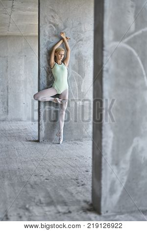 Blonde ballerina leans on the concrete wall on the floor of the unfinished building. She wears a green leotard with light leggings and pointe shoes. She stands on left toe and looks into the camera.