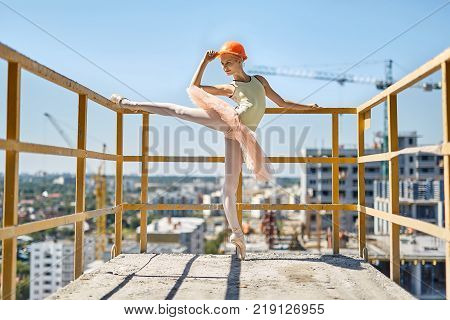 Happy ballerina stands on the left toe on the concrete balcony of the unfinished building on the cityscape background. She wears green leotard, peach tutu, leggings, pointes and construction helmet.