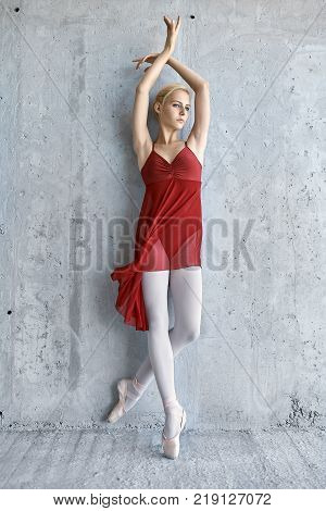 Elegant ballerina leans on the concrete wall with outstretched arms. She wears a red skirted leotard with light leggings and pointe shoes. Girl looks to the side. Sun shines onto her body. Vertical.