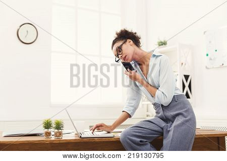 Making business call. Serious african-american ceo businesswoman talking on mobile in modern office, while working on laptop, copy space