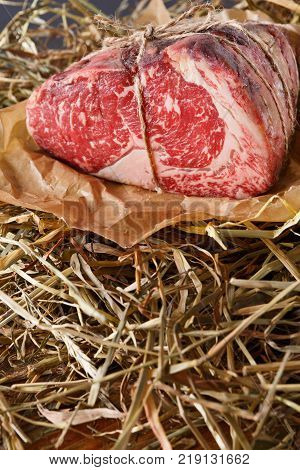 Raw black angus beef bound with rope in craft paper on straw. Aged prime marble meat closeup, copy space, vertical