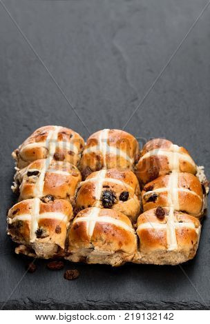 Easter cross buns and sultanas on black stone background