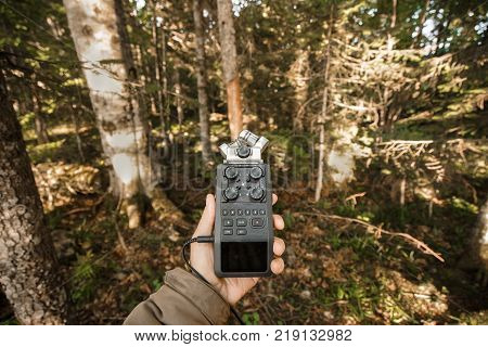 Record sounds and noise of the forest on a digital hand-held microphone. A man holds an audio recorder on the outstretched hand in the thicket of the forest.