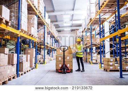 Young female warehouse worker loading up a pallet truck with boxes. A woman unloading boxes.
