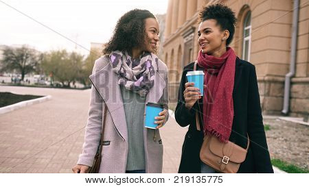 Two beautiful mixed race woman friends drink coffee and talking after shopping and walking city street