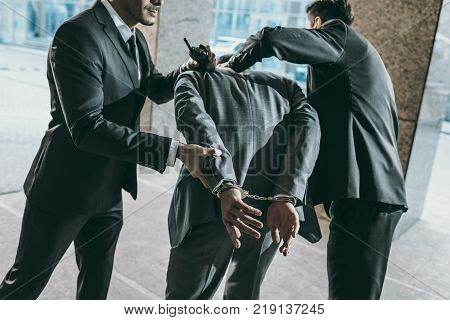 Cropped image of security guards arresting male offender