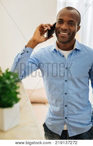 In high spirits. Good-looking alert young man talking on the phone and beaming and enjoying the conversation
