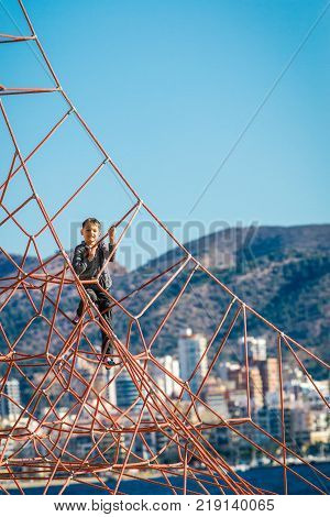 Little boy climbing on the rope at playground in Benidorm beach.