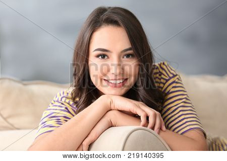 Young beautiful smiling woman resting on sofa at home