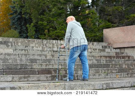 Elderly man with walking frame going up the stairs outdoors
