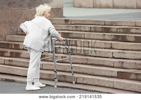 Elderly woman with walking frame going up the stairs outdoors