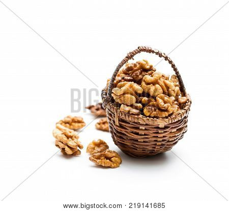 Walnut kernels in a small wicked basket isolated on white