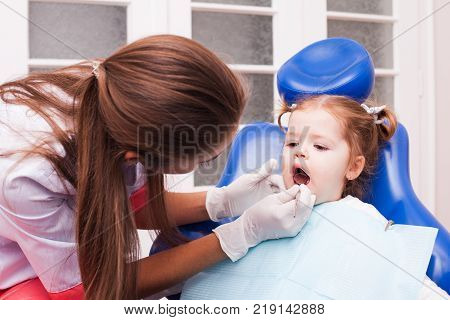 Two years old girl is on the first visit in the dental office. Young  attractive