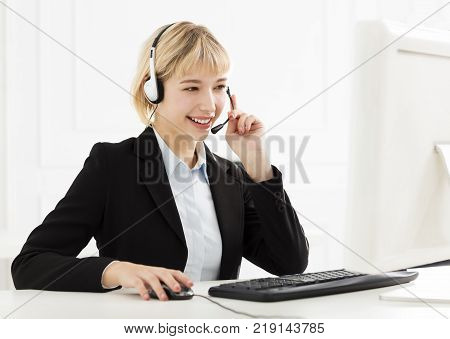 young smiling business woman with headset  in office