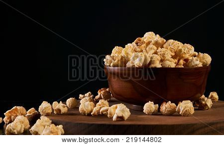 Popcorn in wooden bowl on black background with copy space, close-up. Sweet caramel popcorn. Movie time concept