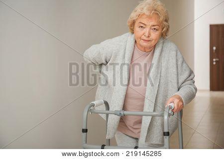 Elderly woman with walking frame in corridor