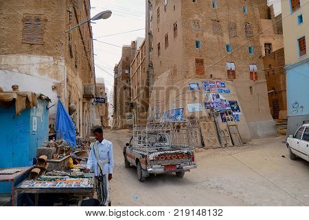 SHIBAM, YEMEN - SEPTEMBER 12, 2006: View to the street with market stall and car passing in Shibam, Yemen.