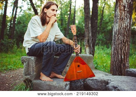 man holds in hands a balalaika in the woods