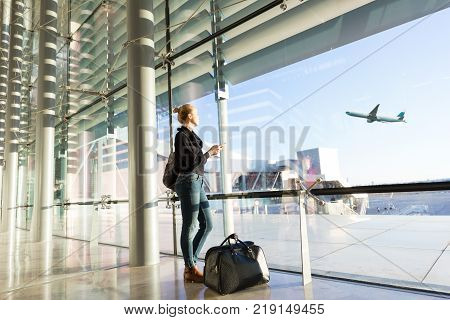 Young casual female traveler at airport, holding smart phone device, looking through the airport gate windows at planes on airport runway.