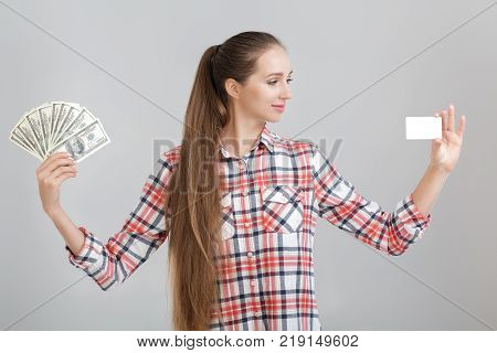 woman in plaid shirt holds dollar bills and plastic card. choice between cash and credit card