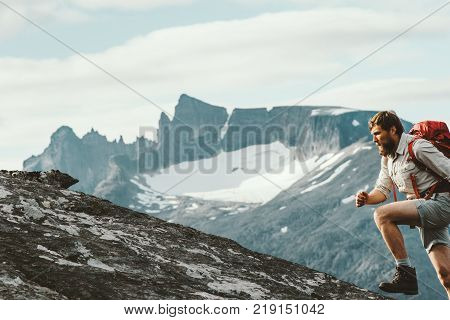 Active Man running in mountains with backpack Norway Travel hiking lifestyle concept active weekend summer vacations skyrunning sport
