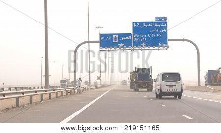 ABU DHABI, UNITED ARAB EMIRATES - APRIL 3rd, 2014: Trucks driving on a desert motorway in the United Arab Emirates with heat haze.