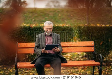 Grandpa use a tablet sitting in the pakr on the bench.