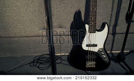 Bass guitar stand beside microphone tripod and absorb wall in the sound studio production.