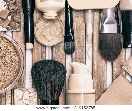 Make-up products to even skin tone and complexion. Corrector, powders, concealer stick, liquid foundation, make up brushes. Top view, toned