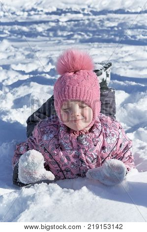 Girl lying on belly in the snow hands in front. The girl narrowed her eyes and wrinkled my nose and smiles. She was pleased and happy. Kid loves the winter holidays.