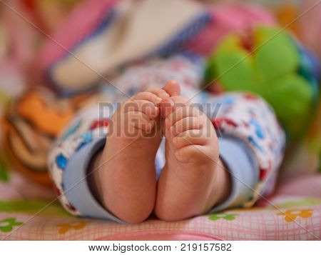 Two legs of a small baby in pajamas, Who still does not know how to walk.
