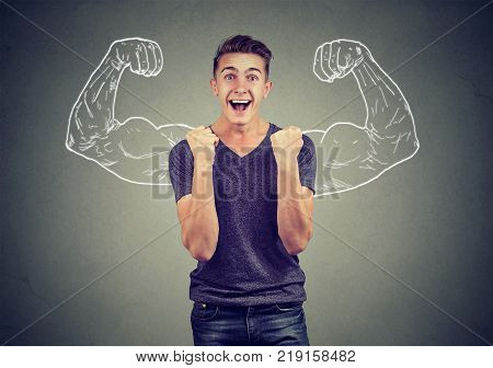 Successful man winning fists pumped celebrating success flexing muscles isolated on gray wall background. Positive human emotion facial expression. Life perception