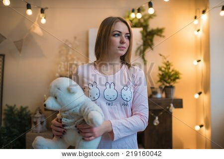 young beautiful woman in a room decorated for celebrating the new year and christmas