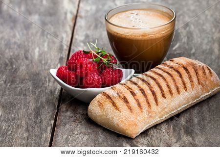 homemade fresh panini bread with cup of cappuccino and raspberries