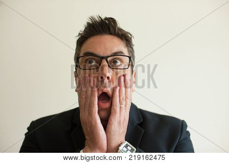 Close-up of terrified face of mid adult Caucasian businessman wearing eyeglasses holding head in hands. Shock and fear concept