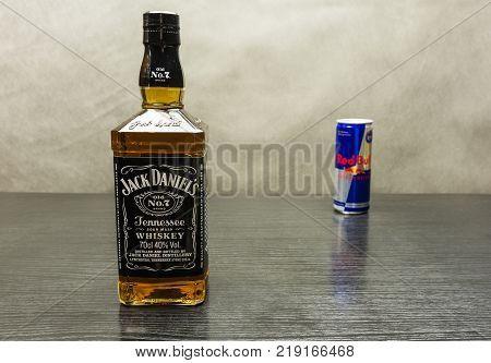 Niedomice Poland - December 20 2017: A bottle of whiskey - Jack Daniel's. In the background the Red Bull energy drink.