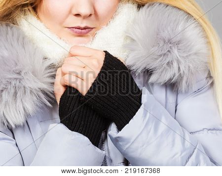 Seasonal fashion clothes and clothing concept. Woman wearing light winter warm furry coat feeling very cold warming herself up.