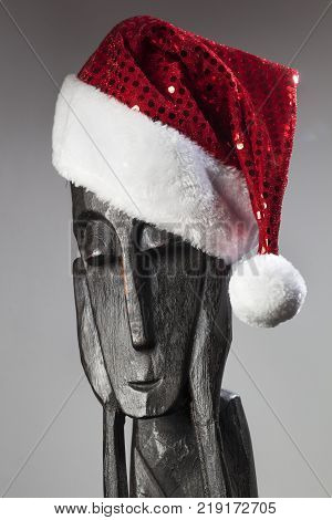 Wooden African statue of a thinker with Santa hat