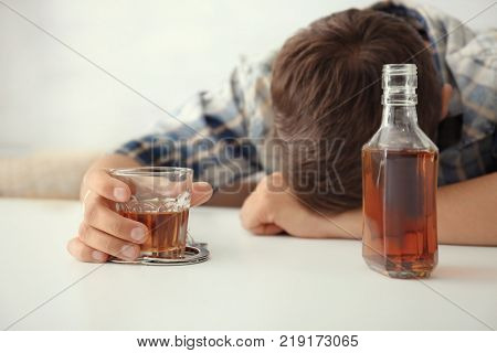 Drunk man in handcuffs with glass and bottle of alcohol sitting at table indoors. Alcohol dependence concept