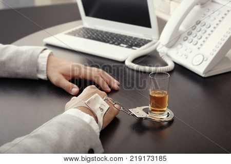 Man in handcuffs sitting at table with glass of brandy. Alcohol dependence concept