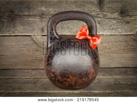 Red bow on Old rusty Kettlebell over wooden table Father's Boss's day concept