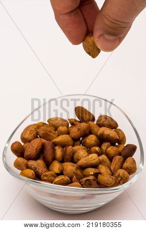 person droping pealed hazelnuts to the glass bowl