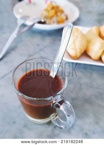 A glass of Thai traditional drink on blurred background - top view; Multi-layered of hot coffee and sweetened condensed milk; Selective focused; vintage style colour; Copy-space on top