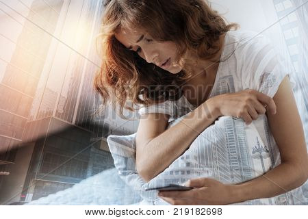 Some difficulties. Depressed brunette bowing head and embracing pillow while looking at her telephone