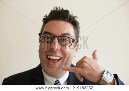 Close-up of happy face of mid adult Caucasian businessman wearing glasses showing calling gesture, looking at camera and smiling. Business communication concept