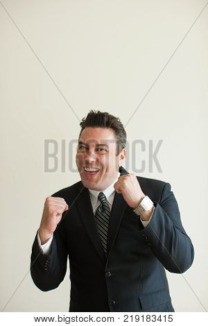 Portrait of happy mid adult Caucasian businessman standing in boxing pose, looking at camera and smiling. Competition and challenge concept